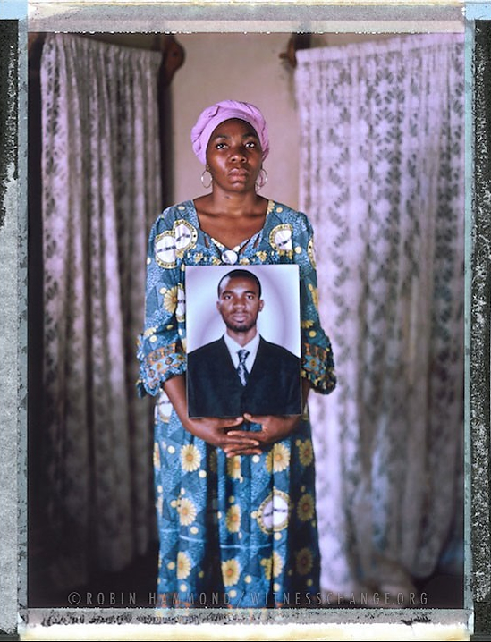 """A posed portrait of the older sister of LGBT Activist and Journalist Eric Lembembe (in the picture she is holding), Ndongo Alice, 37, at home in Yaounde. Eric and Alice were very close when they were growing up. There was gossip in the family about his sexuality but Eric was never open about being gay. Eric was an outspoken campaigner for LGBT rights in Cameroon though and critical of state sponsored discrimination. Eric was murdered on the weekend of July 15/16, 2013. Eric had been brutally tortured. His legs, arms, and neck were broken. He had burns on his body from an iron.  The corners of his mouth were sliced, his eyes had been gouged out, as had his tongue. Before his death Eric had told his sister, Alice, that he had many problems but he refused to share them with her. After his death Alice found out he had been threatened many times. After his death she also received threats. One SMS said """"You will die like your fag brother"""".  Eric's death has profoundly affected the family: """"By loosing Eric we have also lost our mother. She has changed completely, her health, everything. And I feel really lonely without him. He was really helping me."""" Eric's killer/s have never been caught. Yaounde, Cameroon. December 2014.  While many countries around the world are legally recognizing same-sex relationships, individuals in nearly 80 countries face criminal sanctions for private consensual relations with another adult of the same sex. Violence and discrimination based on sexual orientation or gender expression is even more widespread. Africa is becoming the worst continent for Lesbian, Gay, Bi-sexual, Transgender, Queer, Inter-sex (LGBTQI) individuals. More than two thirds of African countries have laws criminalizing consensual same-sex acts. In some, homosexuality is punishable by death. In Nigeria new homophobic laws introduced in 2013 led to dramatic increase in attacks. Under Sharia Law, homosexuality is punishable by death, up to 50 lashes and six months in prison for """