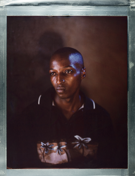 "A posed portrait of 26 year old Aaron, a refugee from the Democratic Republic of Congo living in Kakuma Refugee Camp in north western Kenya. When his community learned that he was LGBTQI+  they targeted his family. ""At one time, my family could be attacked by police and they could be imprisoned. I could be tortured, I could be beaten sometimes. And then, one time, my family was attacked in the middle of the night. They came at my home. They kicked the front door of our house. They entered, searching for me. I sensed there was danger and I had to slip through the door of the back house of our house, and I ran away to the bush. I don't know what happened to my family. And I ran into Uganda. I ran from Uganda to Kenya. Right now I'm here as a refugee, and I'm living in Kakuma Refugee Camp. That's the end of my story."" Kenya, October 2017.  The Kakuma Refugee Camp is located in north western Kenya and houses more than 180,000 refugees. The camp is located in a semi-arid desert with temperatures over 30C. LGBTQI+ refugees are a minority; approximately 190 total with 120 Ugandans, and are often targeted by the wider refugee community. The camp, run by the UNHCR, provides food and medical support, however rations meant for a month typically last just two weeks. Treatment facilities are located miles away, and transport is not provided, posing a challenge for those with HIV / AIDS requiring life-saving medication. While in many places, there has been great progress in recent years in the movement for lesbian, gay, bisexual, transgender, or intersex (LGBTQI+) rights, including an increasing recognition of same-sex marriage, nearly 2.8 billion people live in countries where identifying as LGBTI is subject to rampant discrimination, criminalization, and even death. Same-sex acts are illegal in 76 countries; in some countries, this can result in being sentenced to death. Behind these statistics, there individuals with unique, often harrowing stories. Where Love Is Illegal was created to tell those stories.  Robin Hammond/NOOR for Witness Change"