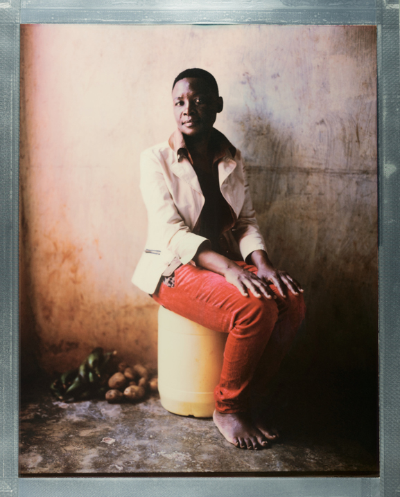 """A posed portrait of Nakitende Aisha in Nairobi. Aisha knew she was lesbian when she was 13 years old. She describes her family's reaction: """"My family members want to kill me after they found out that I am a lesbian. Even villagers wanted to kill me. My family told the villagers that in case they saw me, they should kill me. That my family would pay them."""" Her village was not safe, but neither were the streets of Kampala, Uganda's capital. In 2000 walking back from the country's only LGBT bar (since closed by the President) she was beaten with a metal pole and gang raped. """"I get to realise I was sick in 2014. That is after I started to fall sick frequently which was never the case for me."""" Aisha tested positive for HIV. Given that she did not have sex with men, she presumes she contracted the disease when she was raped. Fearing for her life she fled her native Uganda for Kenya. She describes how life is here in the country where she seeks sanctuary: """"Even in Kenya, the neighbours don't like me. They abuse me saying I am a disgusting lesbian… we are not at peace even here in Kenya."""" She has continued to face attacks here in Kenya and after one particularly violent one, lives in fear: """"I am always scared, worried that they could come back and kill me because they had machetes and they were 15 in number. So I worry that they could come back and behead me… my heart has never been at peace since then. It is always pumping hard. I am always worried that those men could come back and kill me here in Kenya."""" Aisha, like all LGBTQI+ refugees in Kenya hopes to be resettled to a country that will accept her for who she is. The emotional turmoil of her circumstances, and lack of any hope weighs heavily on her: """"For the future, I feel like committing suicide because I am not happy at all here in Kenya… Only God knows. We are just strong hearted but people hate us."""" Kenya, October 2017.  Nature Network is a Nairobi based organization providing LGBTQI+ refugees in Kenya with suppor"""