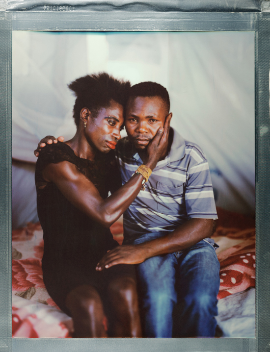 "A posed portrait of Kuteesa (left) and Ernest (right) who met at Kakuma refugee camp in north western Kenya. Kuteesa identifies as a transgender woman and Ernest as gay. Both fled their home country of Uganda seeking sanctuary in Kenya as refugees. They found neither safety, nor hope. Even the refugee camp, run by the UN is not safe. They suffer death threats and discrimination from others in the camp. Moving around is not safe as Kuteesa explains: ""Whenever we try to fetch water, there are so many people outside there who are not gays because we lack piped water in our home, even going out to buy some food; the shops don't sell to us.  They refuse to sell to you because you are gay and that is why we no longer purchase some things."" Even seeking health care is not safe. Kuteesa says ""We are so far from the hospitals and so can't walk there because if you do, you can be stoned to death. Even if you are sick, you have to just suffer in case you fail to get someone to escort you to the hospitals… Everywhere you go, people ridicule you, and we are so misery now."" Both hope to be resettled: ""I would like for us to have enough freedom to live freely without having to hide our feelings in public just like it is in some foreign countries"" says Kuteesa. Kenya, October 2017.  The Kakuma Refugee Camp is located in north western Kenya and houses more than 180,000 refugees. The camp is located in a semi-arid desert with temperatures over 30C. LGBTQI+ refugees are a minority; approximately 190 total with 120 Ugandans, and are often targeted by the wider refugee community. The camp, run by the UNHCR, provides food and medical support, however rations meant for a month typically last just two weeks. Treatment facilities are located miles away, and transport is not provided, posing a challenge for those with HIV / AIDS requiring life-saving medication. While in many places, there has been great progress in recent years in the movement for lesbian, gay, bisexual, transgender, or intersex (LGBTQI+) rights, including an increasing recognition of same-sex marriage, nearly 2.8 billion people live in countries where identifying as LGBTI is subject to rampant discrimination, criminalization, and even death. Same-sex acts are illegal in 76 countries; in some countries, this can result in being sentenced to death. Behind these statistics, there individuals with unique, often harrowing stories. Where Love Is Illegal was created to tell those stories.  Robin Hammond/NOOR for Witness Change"
