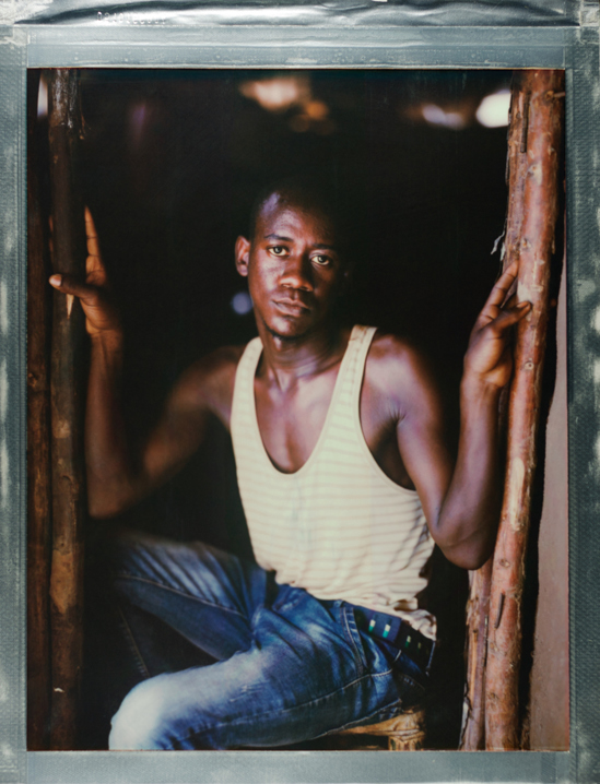 """A posed portrait of Sudi from Rwanda, who was born HIV positive, to a HIV positive mother. He hid being gay for 24 years, but after coming out, was forced to leave home and is now in Kakuma Refugee camp. """"People used to point to me, I cannot fetch water. That why I come to hide here, myself, the best way that isn't people who doesn't know me, who doesn't know my status, who doesn't know that I'm LGBTI, who doesn't know that I'm infected by HIV. I live like someone who doesn't have a home. To be a refugee is something that make me first to be pain. We used to face a lot of issues in camp. Today I breathe, tomorrow I cannot breathe. That is the way we live."""" Sudi is choosing to be open about his HIV status hoping to reduce the stigma others with HIV/AIDS feel. """"I told those people who have hormones like me, to be open, who have infected of HIV, to be open. To have HIV doesn't mean that you can die. I live until now. I go to things, use your medicine, and don't think a lot."""" Sudi believes that a community should support each other: """"This is a message I pass to your friends: if you know your friend have a problem, don't run from him. You two are like that. Stay with him. Give him hope. All of the world is not in Kakuma only. Every place where there's LGBTI like us, help them."""" Kenya, October 2017.  The Kakuma Refugee Camp is located in north western Kenya and houses more than 180,000 refugees. The camp is located in a semi-arid desert with temperatures over 30C. LGBTQI+ refugees are a minority; approximately 190 total with 120 Ugandans, and are often targeted by the wider refugee community. The camp, run by the UNHCR, provides food and medical support, however rations meant for a month typically last just two weeks. Treatment facilities are located miles away, and transport is not provided, posing a challenge for those with HIV / AIDS requiring life-saving medication. While in many places, there has been great progress in recent years in the movement for lesbian, gay, b"""